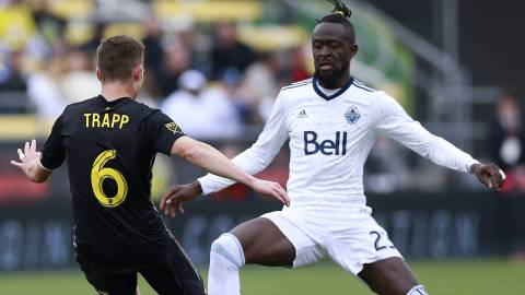 Columbus Crew midfielder Wil Trapp (6) looks for a way around Vancouver Whitecaps forward Kei Kamara (23) in the first half of an MLS soccer game in Columbus, Ohio, Saturday, March 31, 2018. (Brooke LaValley/The Columbus Dispatch via AP)
