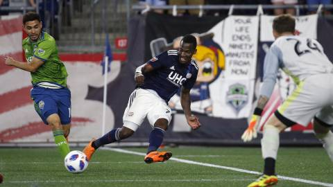 New England Revolution's Cristian Penilla, center, tries to get a shot past Seattle Sounders goalie Stefan Frei (24) during the second half of an MLS soccer game in Foxborough, Mass., Saturday, July 7, 2018. (AP Photo/Michael Dwyer)
